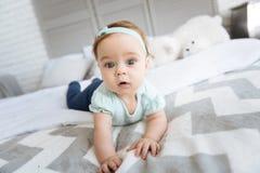 在家说谎在床上的惊奇的可爱的小孩女孩 免版税库存照片