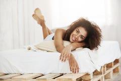 在家说谎在床上的美丽的愉快的非洲女孩微笑看照相机 免版税图库摄影