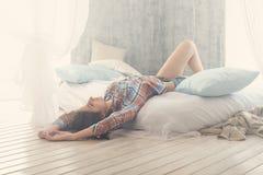 在家说谎在床上的美丽的浪漫妇女/女孩浅黑肤色的男人在她的屋子里 穿戴的偶然衬衣,太阳光,被定调子的温暖的颜色 免版税库存图片