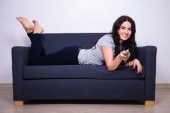 在家说谎在沙发和观看的电视的愉快的妇女 免版税库存照片