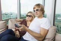 在家戴3D眼镜和看电视的轻松的夫妇 免版税库存照片