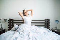 在家streching在床上的秀丽妇女的愉快的早晨 免版税图库摄影