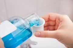 在容器的人倾吐的液体 库存图片