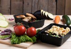 在容器的油煎的茄子有烤鸡翅和未加工的蔬菜的在土气背景、西红柿和微greenss 免版税库存图片