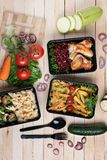在容器的油煎的茄子有烤鸡翅和未加工的蔬菜的在土气背景、西红柿和微greenss 免版税库存照片