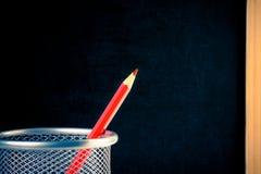 在容器的红色铅笔反对空的黑板 图库摄影