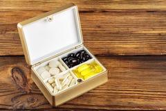 在容器, Ω 3,维生素C,在木背景的胡萝卜素胶囊的混杂的自然食物补充药片 库存图片