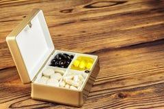在容器, Ω 3,维生素C,在木背景的胡萝卜素胶囊的混杂的自然食物补充药片 免版税库存照片