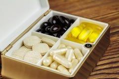 在容器, Ω 3,维生素C,在木背景的胡萝卜素胶囊的混杂的自然食物补充药片 库存照片