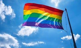 在容忍和采纳的多云天空标志的彩虹旗子 库存图片
