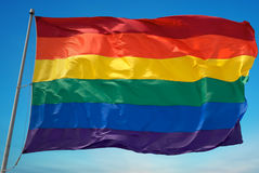 在容忍和采纳的清楚的天空标志的彩虹旗子 免版税图库摄影