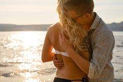 在容忍的微笑的浪漫夫妇在海滩 免版税库存图片