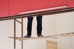 在容易的会破碎的梯子的工作者腿 绘画工作者和危险工作的概念 免版税库存照片