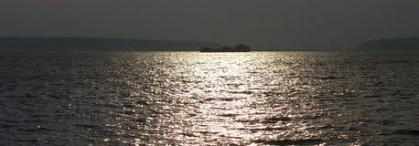 在宽广的安静的河上的日出有漂浮在朝阳的光芒的船的剪影的 黑色和 图库摄影