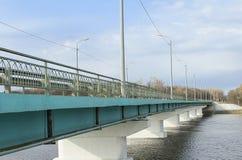在宽广的河,背景的蓝天的长的具体桥梁 免版税库存图片