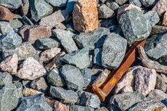 在宽松岩石的生锈的铁路钉 免版税库存图片