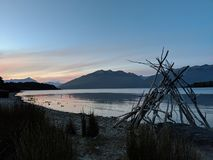 在寂静的湖的豪华幻想日落下午十点与独特的雕塑和当地protectef红色芦苇草 免版税库存照片