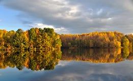 在寂静的水反映的秋叶 图库摄影