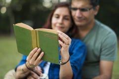 在密林结合花费一起读小说的时间在一顿野餐 图库摄影