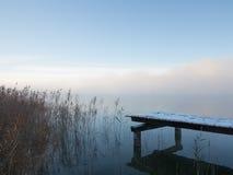 在密集的冬天雾的冷淡的码头与芦苇 库存图片