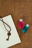 在对小玻璃魔药的顶视图与在粗麻布的健康和马娜不可思议的液体包括表面并且打开空的葡萄酒笔记薄 库存图片