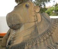 在寺庙之外的杜姆古尔,卡纳塔克邦,印度- 1月1日, 2009巨大的楠迪公牛石头雕象 免版税图库摄影