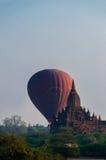 在寺庙后的热空气气球在Bagan 图库摄影