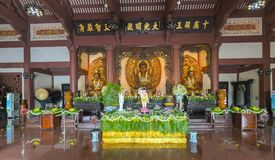 在寺庙的佛教雕象在菩萨` s生日装饰了光,五颜六色的花 库存照片