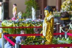 在寺庙的佛教雕象在菩萨` s生日装饰了光,五颜六色的花 免版税库存图片