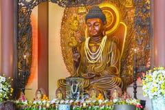 在寺庙的佛教雕象在菩萨` s生日装饰了光,五颜六色的花 图库摄影
