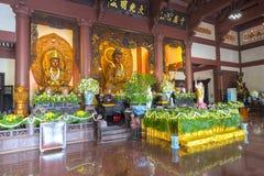 在寺庙的佛教雕象在菩萨` s生日装饰了光,五颜六色的花 库存图片