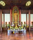 在寺庙的佛教雕象在菩萨` s生日装饰了光,五颜六色的花 免版税库存照片