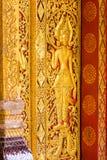 在寺庙的墙壁上的浅浮雕在Louangphabang,老挝 特写镜头 垂直 免版税库存图片
