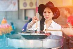在寺庙的妇女灼烧的香火棍子 免版税图库摄影