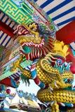 在寺庙的杆附近被包裹的龙 免版税库存图片