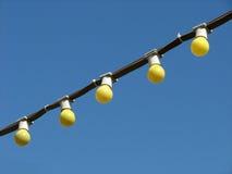 在导线的五个黄色白炽电灯泡在蓝天背景 库存图片