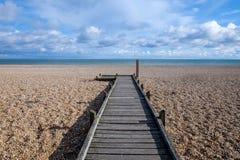 在导致海的Pebble海滩的长的平直的木路 免版税库存照片