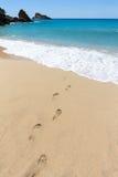 在导致蓝色海的沙滩的脚步在海岸 图库摄影