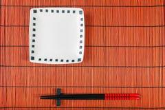 在寿司席子的两双筷子 免版税图库摄影