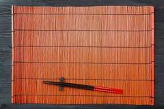 在寿司席子的两双筷子 免版税库存图片