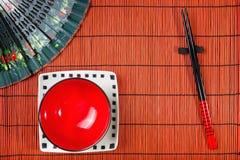 在寿司席子的两双筷子 免版税库存照片