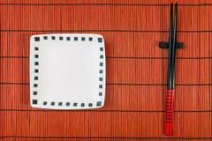 在寿司席子背景的两双筷子 免版税图库摄影