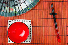 在寿司席子背景的两双筷子 免版税库存图片