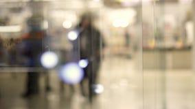 在射击冲走的人民在商业购物中心进来 购物中心的Defocused人 一本诗歌选在购物中心 股票视频