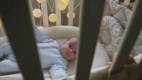 在小儿床的新出生的男婴看照相机 在家在小儿床的逗人喜爱的矮小的婴孩 男婴儿童车覆盖illusytration星期日 股票录像