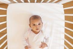 在小儿床的逗人喜爱的女婴 库存图片