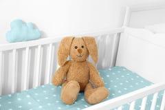 在小儿床的逗人喜爱的软的兔宝宝玩具 库存图片
