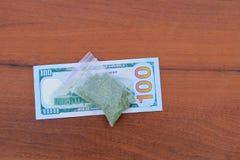 在小包的大麻和100在木桌上的美金 免版税库存照片
