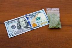 在小包的大麻和100在木桌上的美金 库存照片