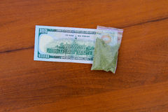 在小包的大麻和100在木桌上的美金 免版税库存图片